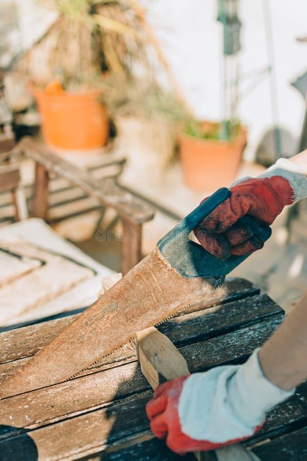 Mujer que asierra una madera, con los guantes del trabajo en la tabla del día fotografía de archivo libre de regalías