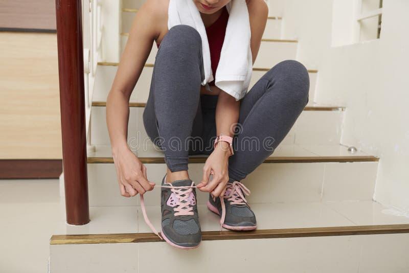 Mujer que ata cordones de zapato fotos de archivo libres de regalías