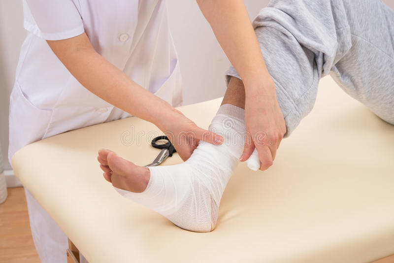 Mujer que ata el vendaje en el pie del paciente fotos de archivo libres de regalías