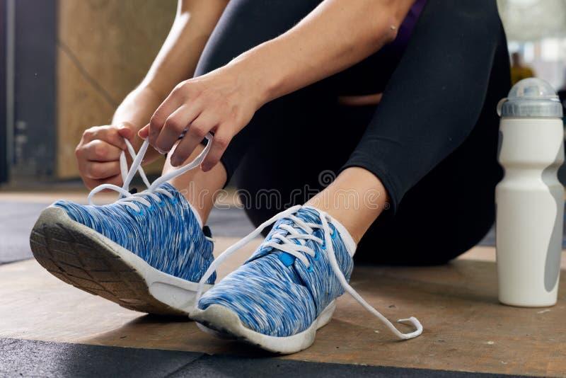 Mujer que ata los zapatos del deporte en gimnasio imagen de archivo
