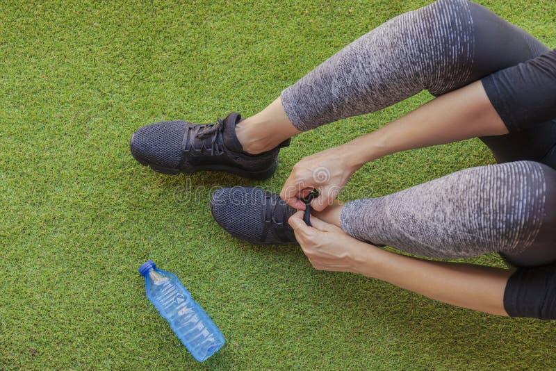 Mujer que ata sus zapatillas de deporte con una botella de agua foto de archivo