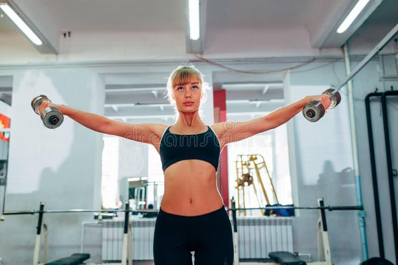 Mujer que aumenta pesas de gimnasia en el gimnasio fotografía de archivo libre de regalías