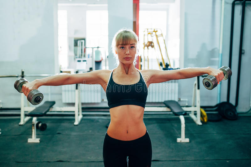 Mujer que aumenta pesas de gimnasia en el gimnasio imágenes de archivo libres de regalías