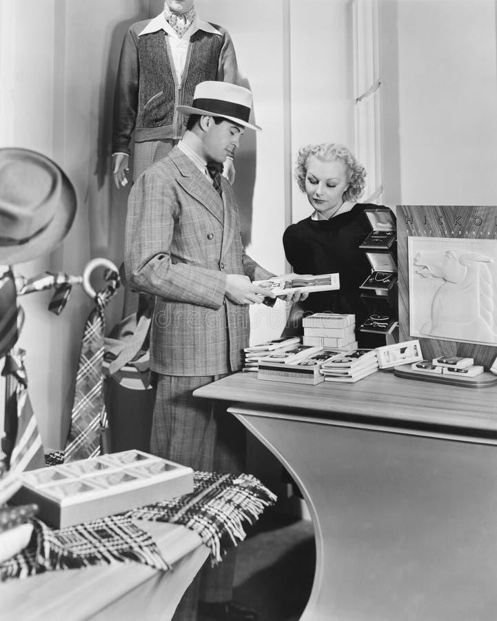 Mujer que ayuda al cliente masculino foto de archivo