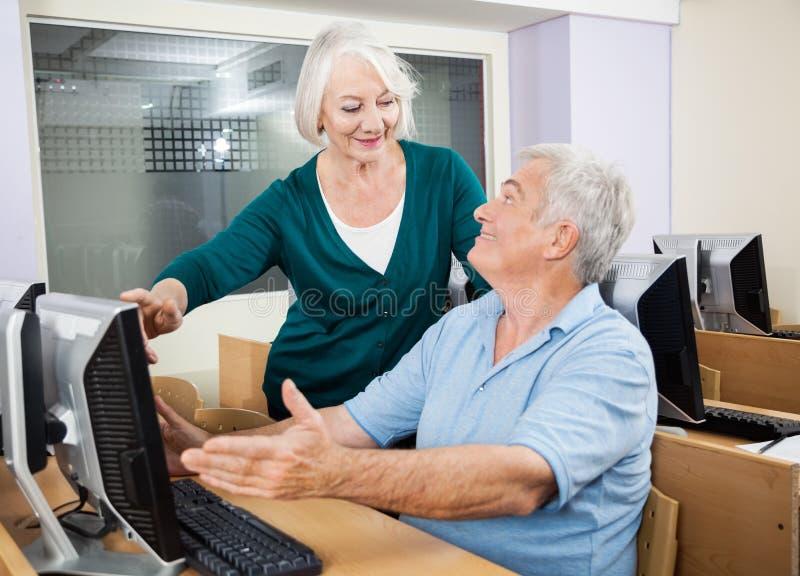 Mujer que ayuda al compañero de clase al usar el ordenador en la sala de clase fotografía de archivo