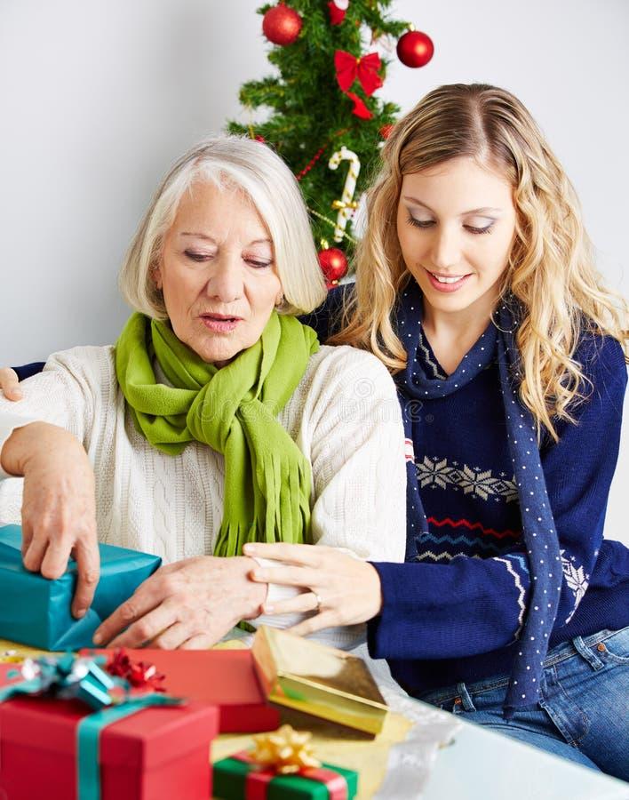 Mujer que ayuda al regalo de embalaje mayor imagen de archivo libre de regalías