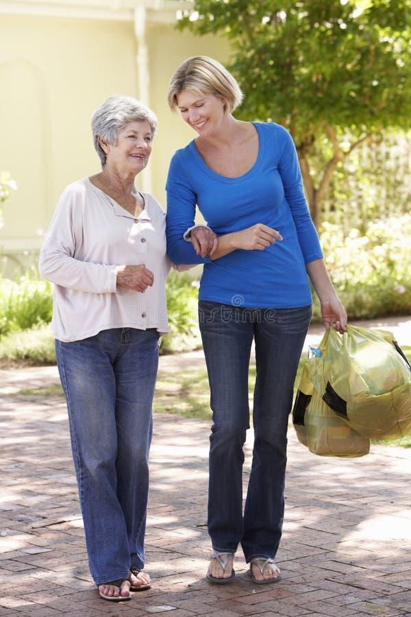 Mujer que ayuda a la hembra mayor con compras fotografía de archivo