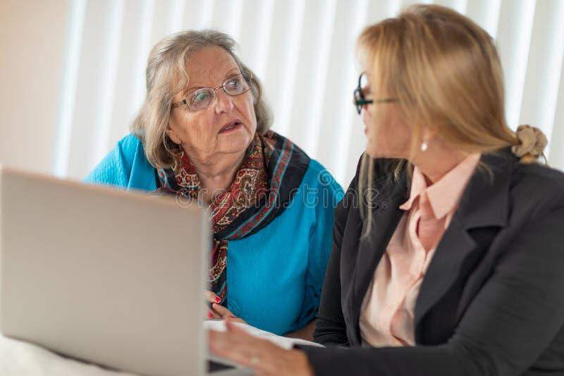 Mujer que ayuda a la se?ora adulta mayor en el ordenador port?til imágenes de archivo libres de regalías