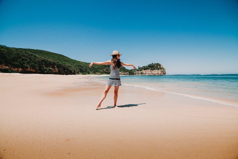 Mujer que baila y que goza de la playa australiana fotografía de archivo