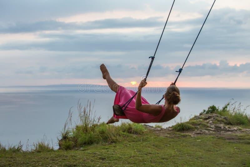 Mujer que balancea en un oscilaci?n en una isla tropical fotos de archivo libres de regalías