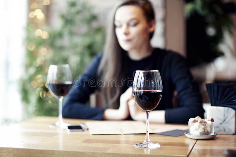 Mujer que bebe el vino rojo en café y que tiene resto cerca de ventana foto de archivo libre de regalías