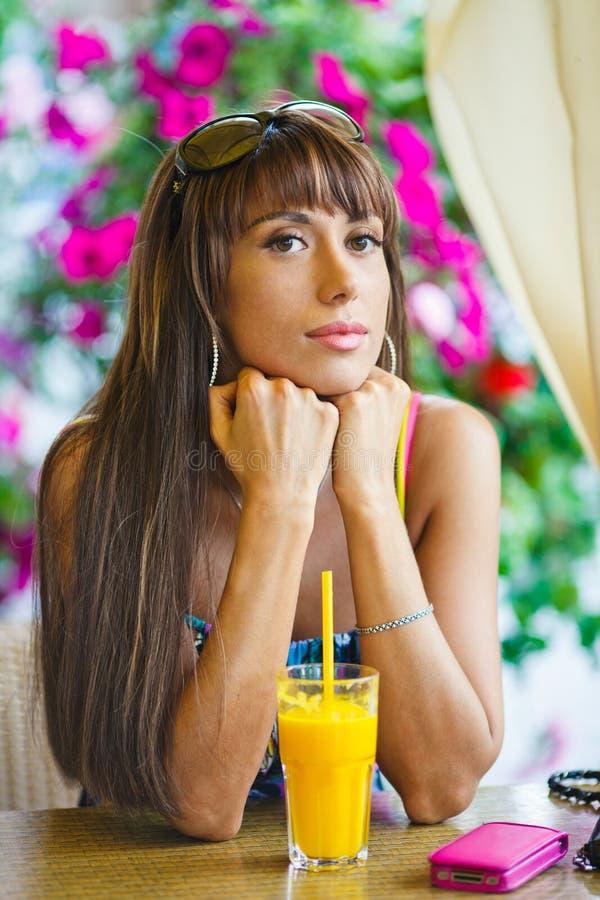 Mujer que bebe el zumo de naranja en café fotografía de archivo libre de regalías