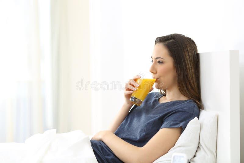 Mujer que bebe el zumo de naranja para el desayuno en una cama fotos de archivo libres de regalías