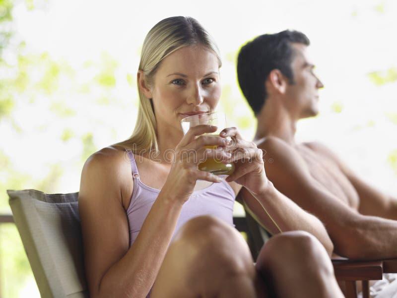 Mujer que bebe a Juice By Shirtless Man imagenes de archivo
