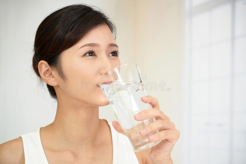 Mujer que bebe un vidrio de agua imágenes de archivo libres de regalías