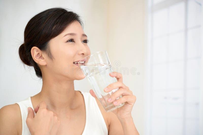 Mujer que bebe un vidrio de agua imagen de archivo