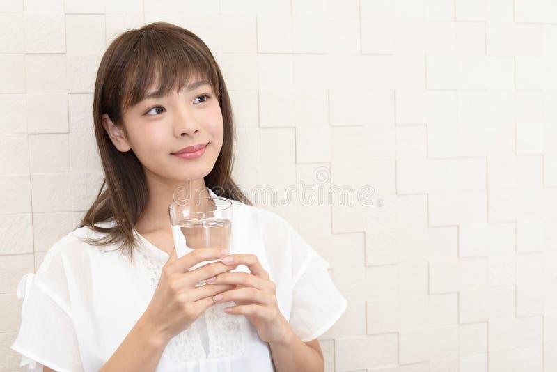 Mujer que bebe un vidrio de agua fotos de archivo