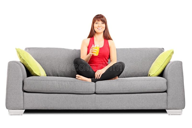 Mujer que bebe un zumo de naranja asentado en el sofá foto de archivo