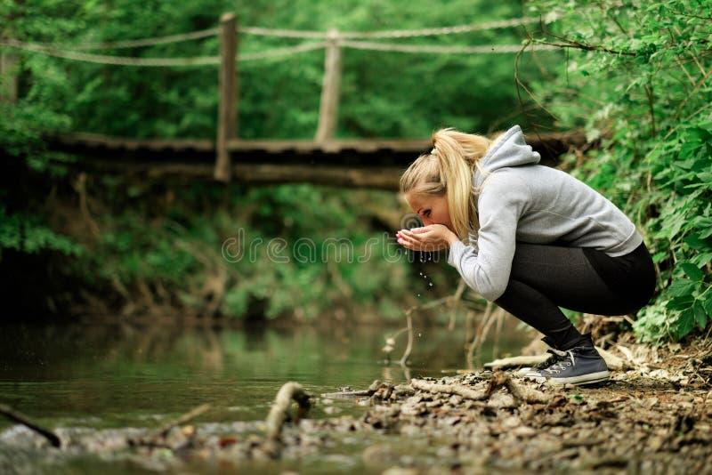 Mujer que bebe una corriente del agua dulce fotografía de archivo