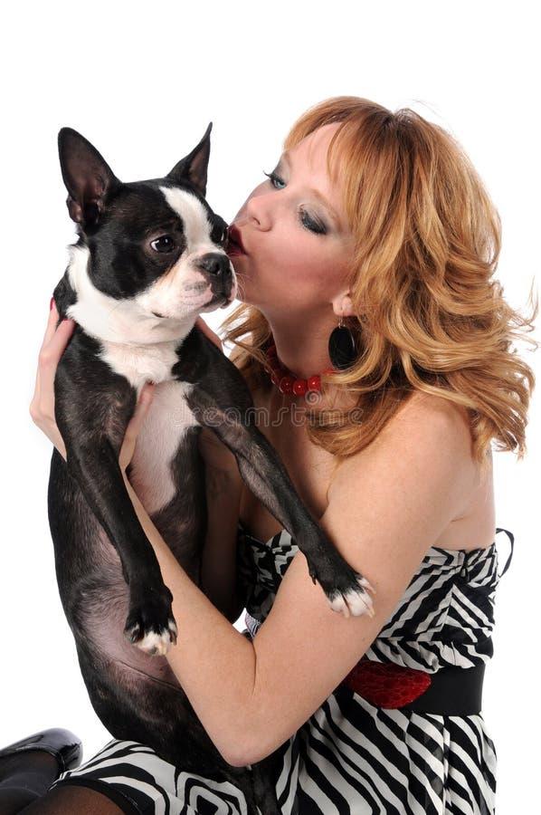 Mujer que besa al terrier de Boston fotos de archivo