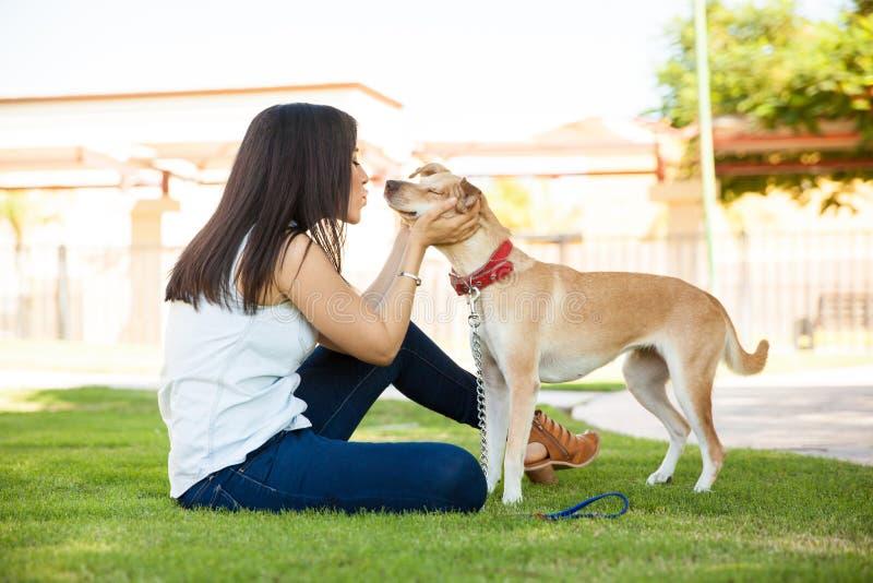 Mujer que besa su perro en un parque fotos de archivo libres de regalías