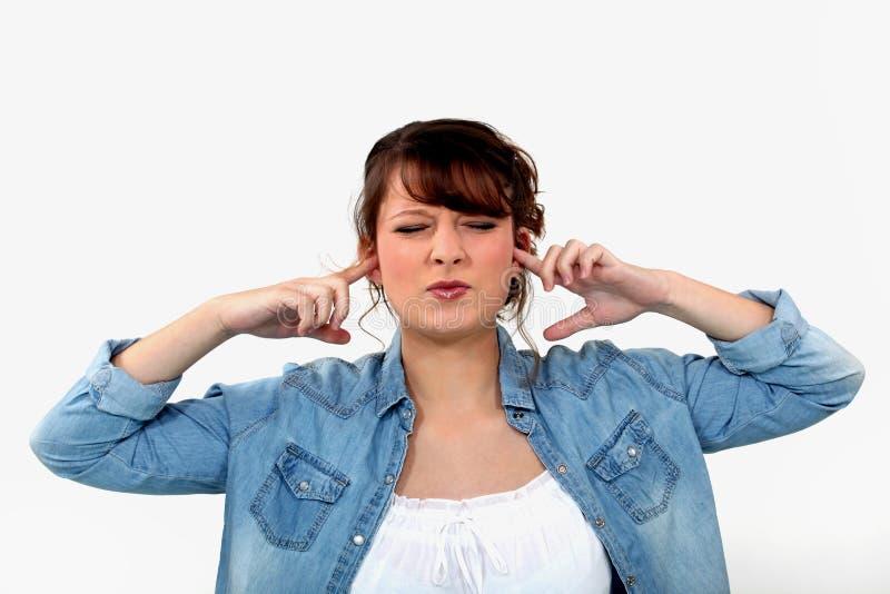 Mujer que bloquea sus oídos foto de archivo libre de regalías
