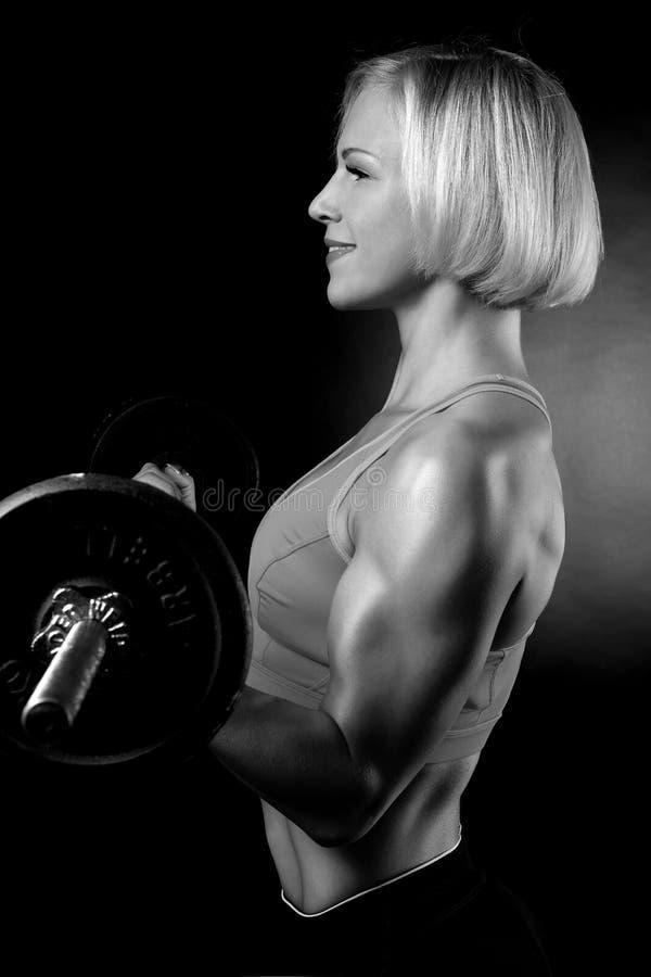 Mujer que bombea para arriba muscules con pesas de gimnasia foto de archivo