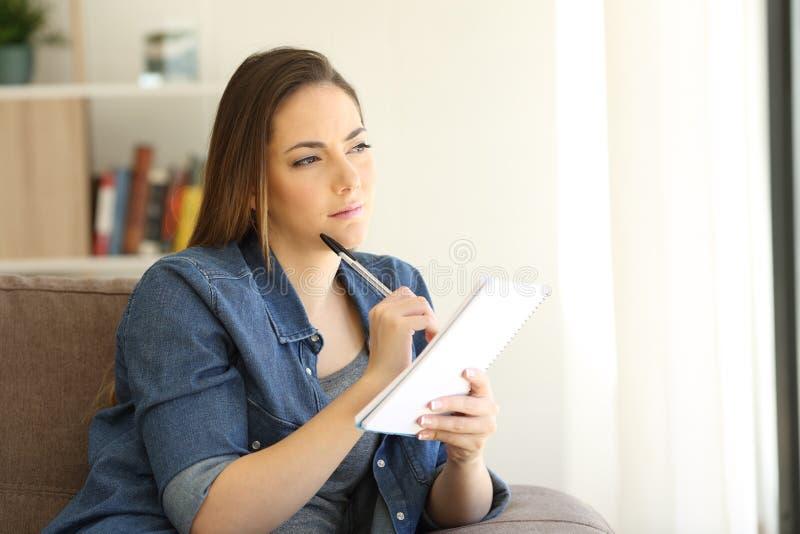 Mujer que busca la escritura de la inspiración en un cuaderno imagen de archivo