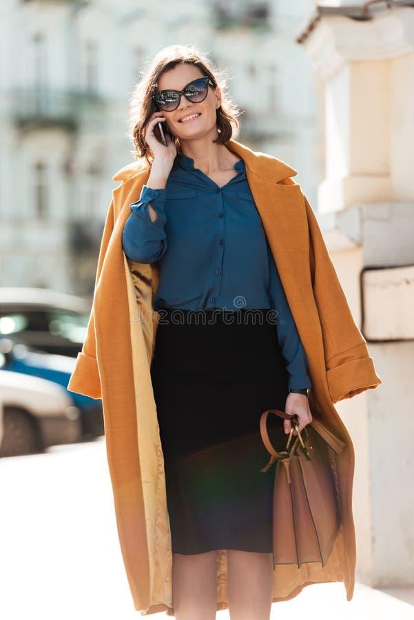 Mujer que camina al aire libre hablando por el teléfono fotografía de archivo libre de regalías