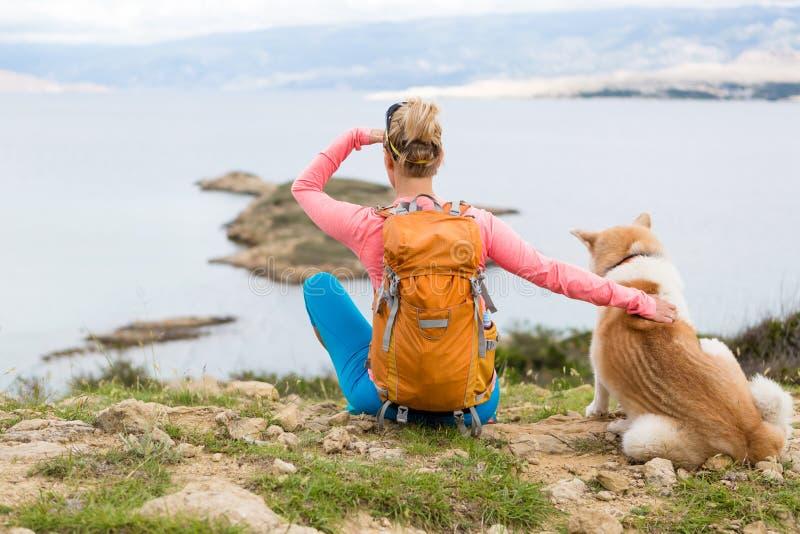 Mujer que camina caminar con el perro en paisaje del mar imagenes de archivo