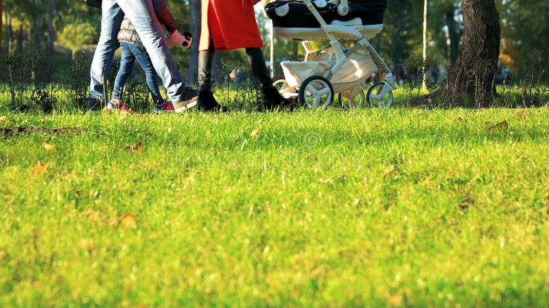 Mujer que camina con el cochecito en parque de la ciudad foto de archivo
