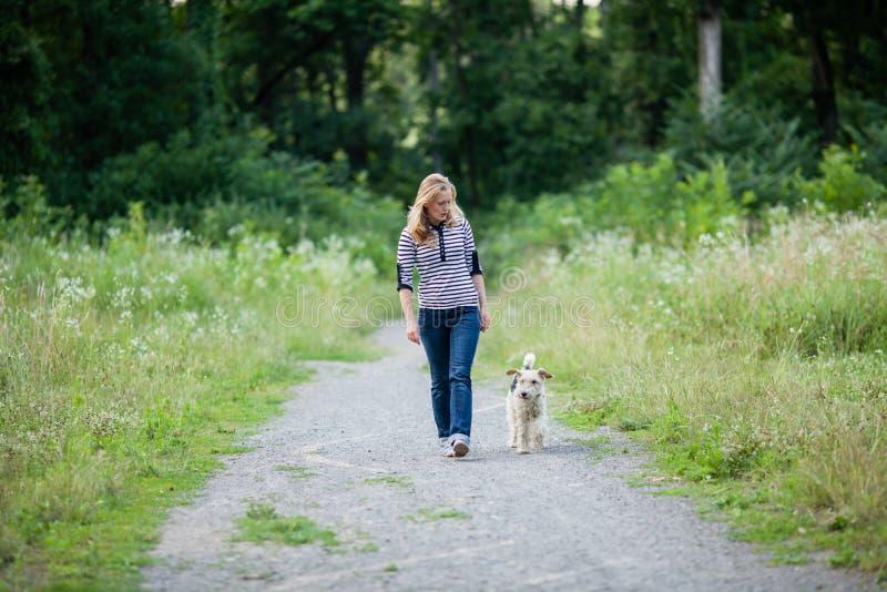 Mujer que camina con un animal doméstico foto de archivo libre de regalías