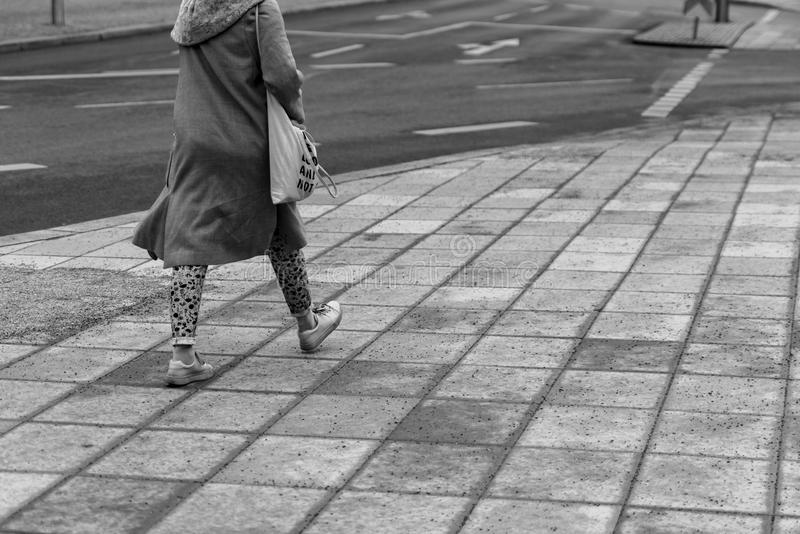 Mujer que camina en blanco y negro en una calle imágenes de archivo libres de regalías