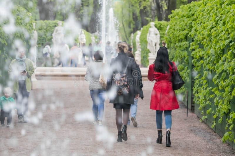 Mujer que camina en capa roja imagen de archivo