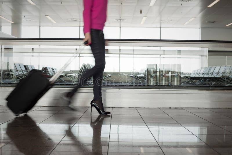 Mujer que camina en el aeropuerto, borroso en el movimiento imagen de archivo libre de regalías