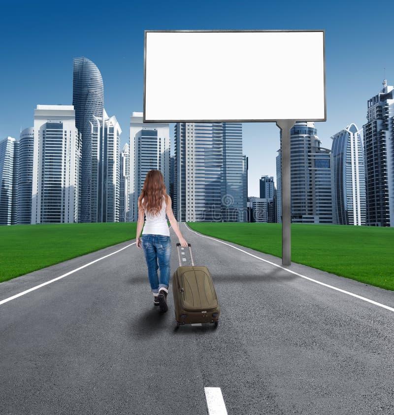 Mujer que camina en el camino a la ciudad, delante de un Bill vacío imagen de archivo