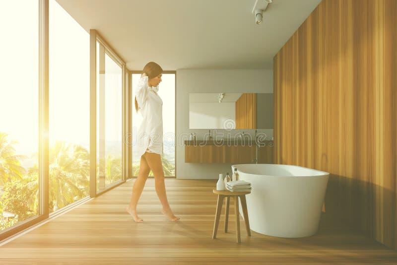 Mujer que camina en el cuarto de baño panorámico blanco y de madera fotos de archivo libres de regalías