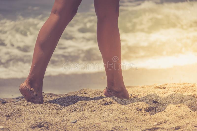 Mujer que camina en el mar, parte del cuerpo, piernas perfectas del ` s de las mujeres que broncean, disfrutando de tiempo en la  fotografía de archivo libre de regalías