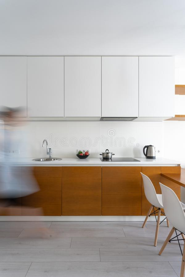 Mujer que camina en el sitio moderno blanco de la cocina foto de archivo