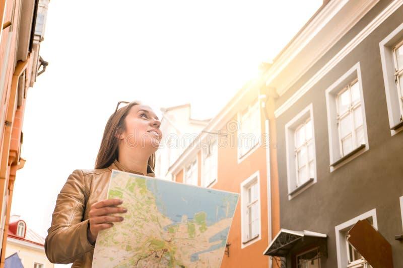 Mujer que camina en la ciudad con el mapa imagen de archivo