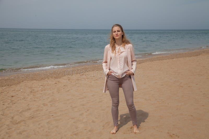 Mujer que camina en la playa arenosa, una costa de mar fotografía de archivo
