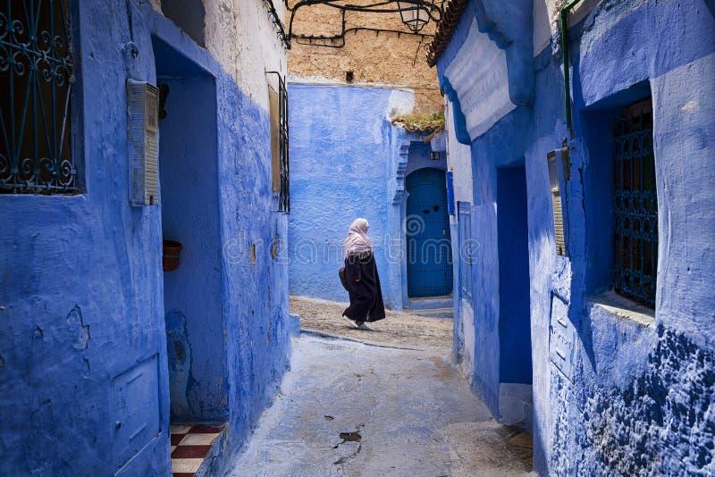 Mujer que camina en una calle de la ciudad de Chefchaouen en Marruecos imagenes de archivo