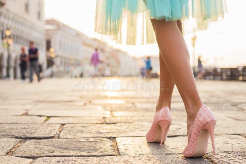 Mujer que camina en zapatos del tacón alto en ciudad vieja imagenes de archivo