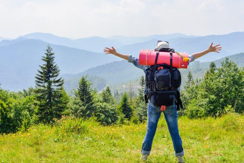 Mujer que camina joven que se coloca encima de la montaña con el valle en el fondo fotos de archivo libres de regalías
