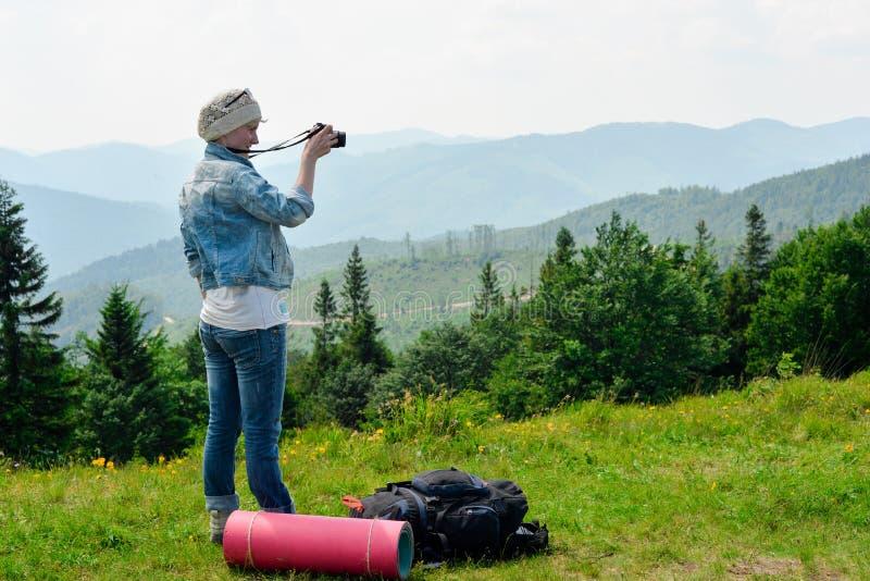 Mujer que camina joven que se coloca encima de la montaña con el valle en el fondo imagen de archivo