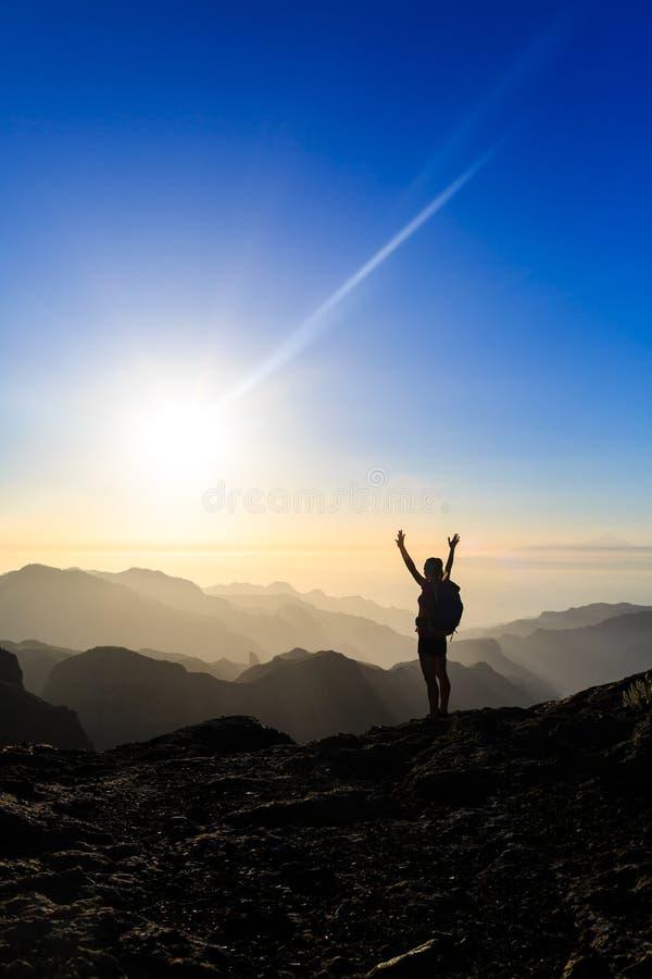 Mujer que camina la silueta del éxito en puesta del sol de las montañas foto de archivo