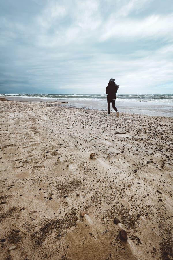 Mujer que camina solamente en la playa en día tempestuoso ventoso fotos de archivo