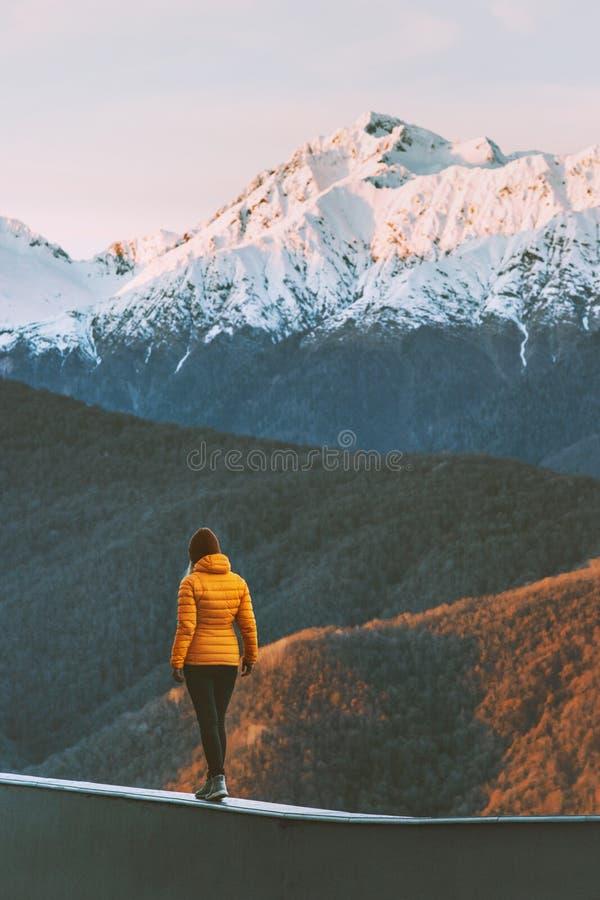 Mujer que camina solamente en vacaciones activas del invierno de la forma de vida de las montañas de la puesta del sol foto de archivo