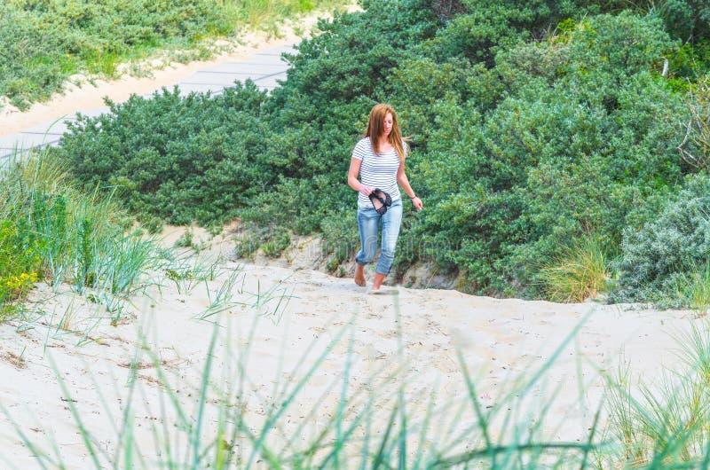 Mujer que camina a través de las dunas de arena fotos de archivo libres de regalías