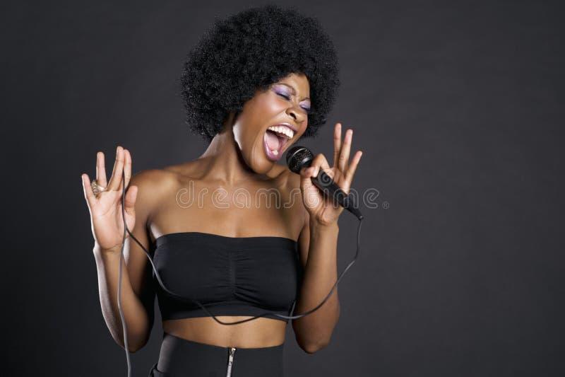 Mujer que canta en el micrófono sobre fondo coloreado fotografía de archivo